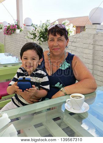 Boy sits with grandmother in outdoor cafe at summer day