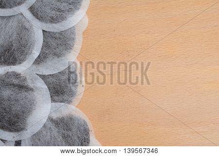 Many round tea bags on brown table - background. Add text.
