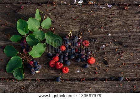 Fresh and ripe shadberry and raspberry with branch and leaves scattered on the weathered wooden table in garden