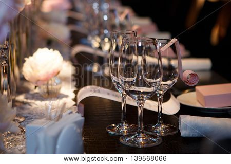 Banquet table, glasses and plates, forks and knives, napkins and buttons for a luxurious celebration in anticipation of guests. Luxury festive table.