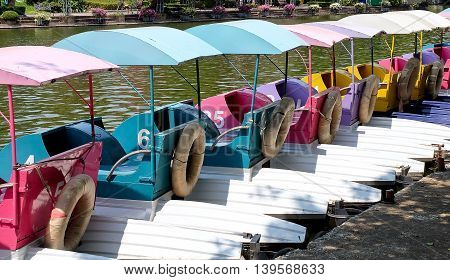 Row of Colorful Water Cycle Boats or Pedal Boats at The Dock in A Park.