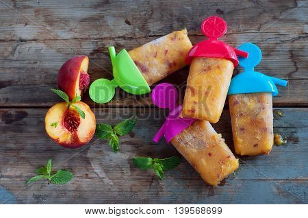 Peach ice lollies with colored sticks on an old wooden table with mint leaves
