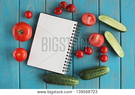 Note book and composition of vegetables on blue wooden desk. Tomato, cucumber. Top view.