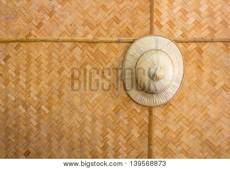Handmade wooden wicker hat hung on a background pattern woven bamboo.