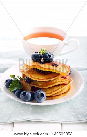 Blueberry pancakes in a stack and cup of tea