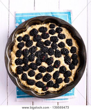 Raw pastry cake with blackberry before baking top view