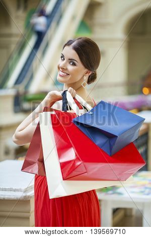 Young beautiful brunette woman with some red shopping bag in the mall