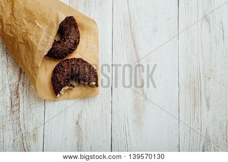 Chocolate Donut In Paper On Wooden Table