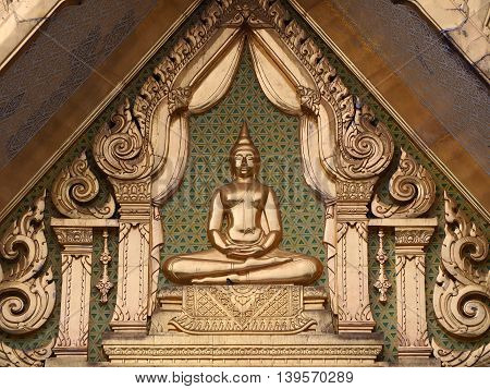 Close up of Golden Buddha on gable chapel.