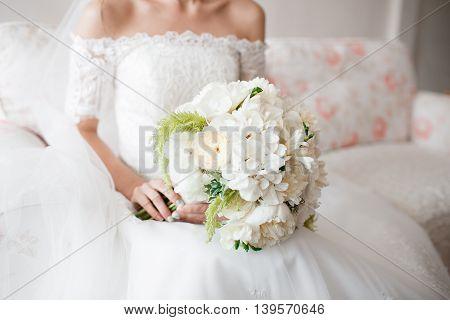 Bride holding wedding bouquet of white Garden rose peony.