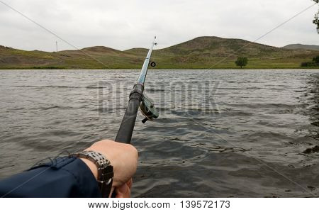 Hand holds an old fishing rod at lake.