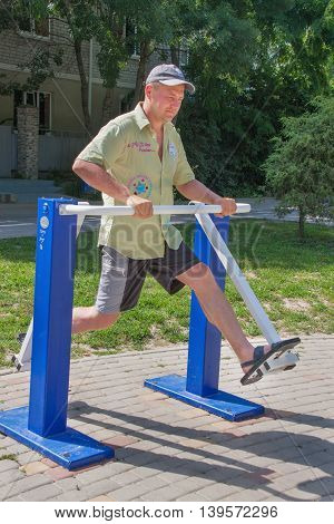 LUGANSK , UKRAINE - MARCH 25, 2016: man doing exercises outdoor sports equipment in the park.