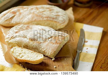 Two loafs of fresh bread and a knife on the board