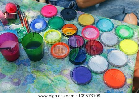 Water paints and paint brush. Watercolor bottle color stains on table