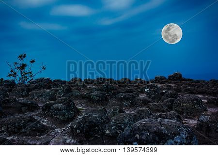 Rocky Against Blue Sky And Beautiful Full Moon At Night. Outdoors.