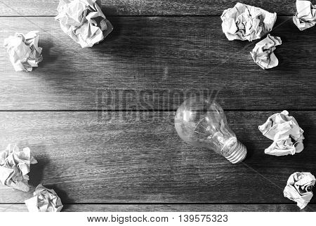 Crumpled paper balls on wooden desk creative writing concept