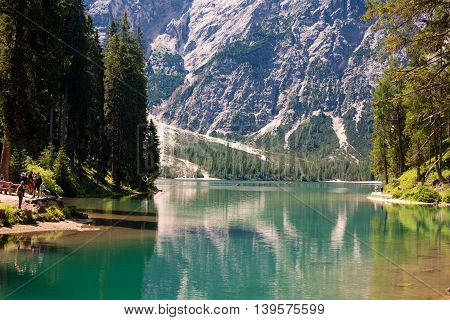 LAKE BRAIES ITALY - JUL 03 2015: Tourists walking around the Lake Braies in the Dolomites with the Seekofel mountain in the background SudtirolItaly