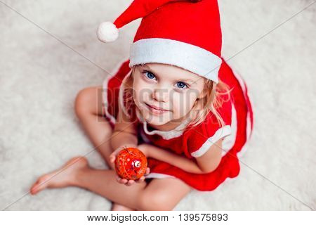 little girl in a red dress and red Christmas Santa hat with Christmas ball in hands looking at the camera and smiling. close-up view from above