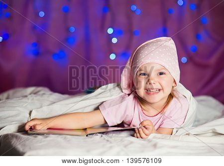 little girl lying in bed in his pajamas in the nightcap on a purple background with Christmas lights and reading a book