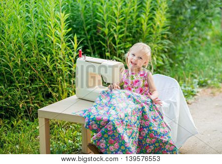 little blonde smiling lovely child 4 years old (girl) in the print dress dress sews on the sewing machine of the beautiful calico cloth on the street