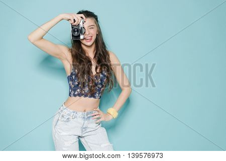 hipster photographer fashion stylish woman dancing and making photo using retro camera. Portrait on blue background in white sweater