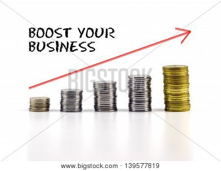 Conceptual Image. Stacks Of Coins Against White Background With Red Arrow And Boost Your Business Wo
