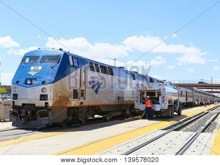 ALBUQUERQUE, USA - MAY 24, 2015: The Amtrak passenger train Southwest Chief being fueled at the station. The tanker is parked next to the engine several passengers are on the platform.