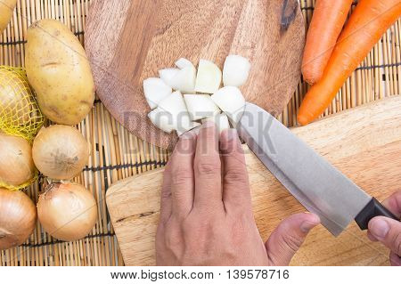 Chef cutting the onion on a wooden board/ Cooking Japanese curry concept