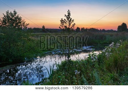 Summer sunset around field with with small river