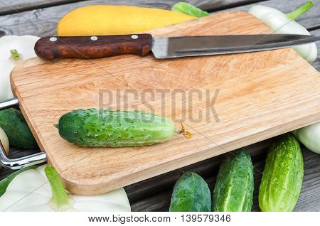 Cutting board, knife, fresh vegetables on wooden table.  Top view with copy space.