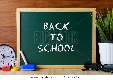 Words Back To School Written On Green Chalk Board On Wooden Table.