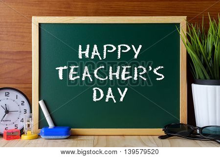 Words Happy Teacher's Day Written On Green Chalk Board On Wooden Table.