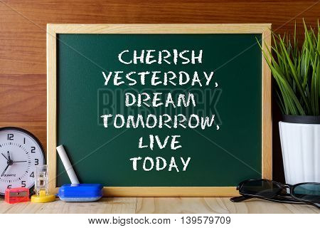 Word Quote Cherish Yesterday,dream Tomorrow,live Today Written On Green Chalk Board On Wooden Table.