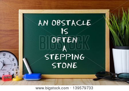 Word Quote An Obstacle Is Often A Stepping Stone Written On Green Chalk Board On Wooden Table.