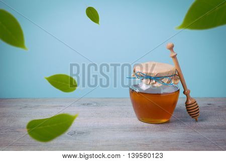 Honey jar mock up template for branding logo design on wooden table with falling green leaves