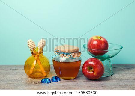 Honey jar apples and pomegranate vase on wooden table. Jewish holiday Rosh Hashana celebration background