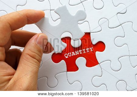 Hand holding a piece of white puzzle with word QUANTITY