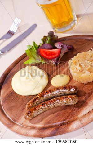 two bratwurst sausages on a wooden plate