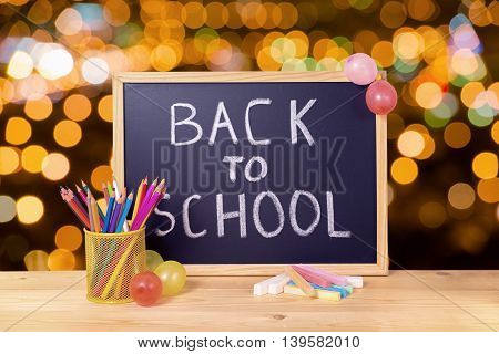 Education Concept With Text Back To School Is Written In Chalkboard, Pen Holder, Colorful Chalks And