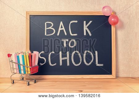 Education Concept With Text Back To School Is Written In Chalkboard, Shopping Cart, Pens, Colorful C