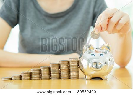 saving money-young woman putting a coin into a money box close up