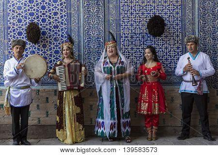 KHIVA, UZBEKISTAN - MAY 23, 2016: Local musicians sing and play ethnic khoresmian music in Khiva, Uzbekistan.