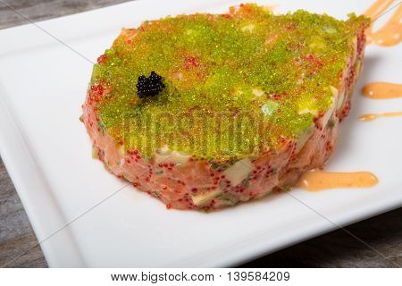 Raw tuna tartare served with caviar on a white plate