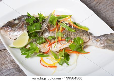 Cooked dorado fish served on a white plate with herbs