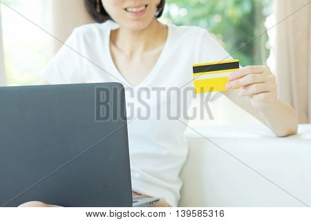 Concept for Internet shopping: woman with laptop and credit card sitting on sofa at home