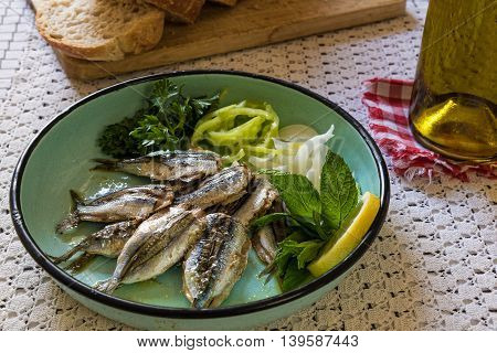 Cooked sardines with green salad in old-fashion plate on table