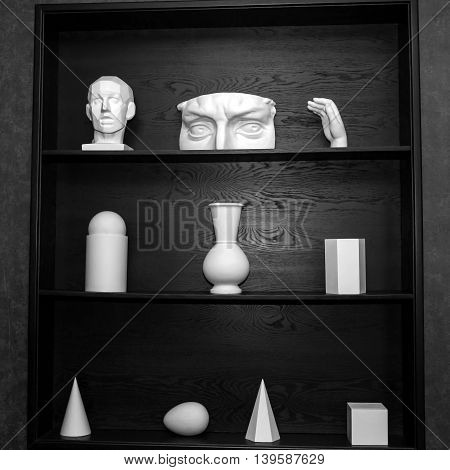 Simple abstract white sculpture. Plaster geometric figures and parts of bodies for art and decorations on a black cabinet