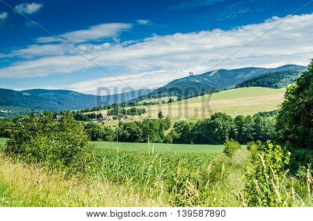 Czech landcape mountains with field close and observation tower far