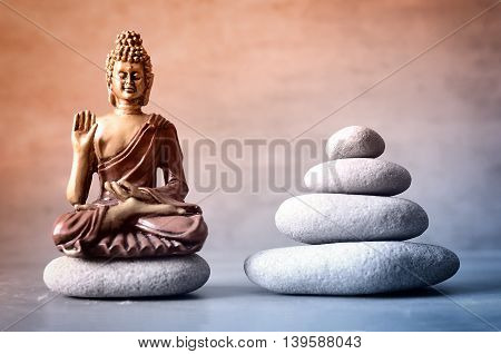 Buddha is sitting in ZEN garden with balance stones.