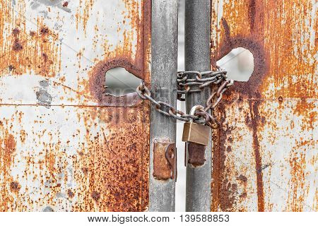 Vintage rusty gate with locked master key and metal chain